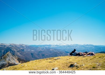 Young Couple Spending Free Time In National Park/mountains,lying On A Meadow.hiking Outdoor Experien