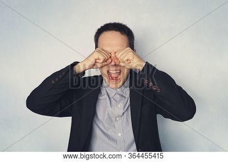 Businessman Screaming And Crying Covering His Eyes With His Hands On Blue Background. Problems In Bu