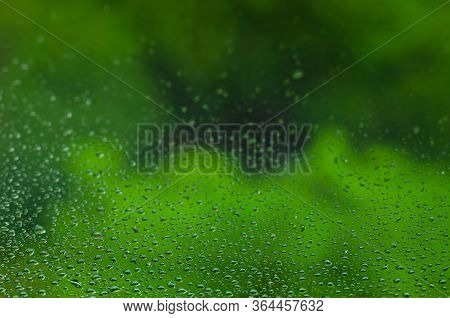 Blurred And Focus Of Rain Drop On Glass Window With Green Color Background In Monsoon Season For Abs