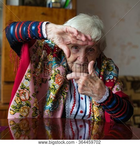 Elderly woman in bright clothes shows by hands gesture photo frame.