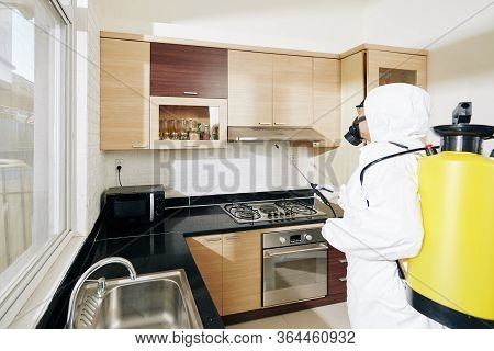 Cleaning Service Worker Desinfecting All Surfaces In Kitchen With Checmical Spray