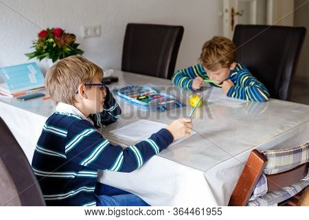 Two Hard-working School Kids Boys Making Homework During Quarantine Time From Corona And Covin 19 Pa