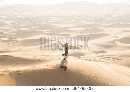 A Husband Photographs His Wife In The Desert. A Married Couple Is Photographed On A Journey Through