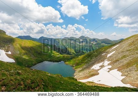 Beautiful Nature Of Romania Mountains. Lake Capra In The Valley. Hills Covered In Grass, Rocks And S
