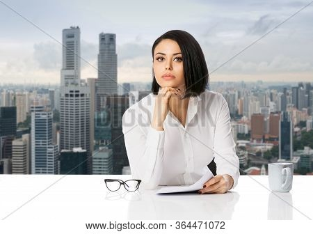Pensive Young Business Woman In White Shirt On Her Desk With Paper Documents Over City Background. A