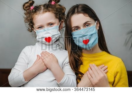 Mothers And Daughter Holding Hands On Breast Sit On Bed, Wear Face Mask With Heart On It As A Way To