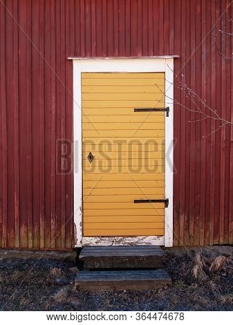 An Old Yellow Door Of A Wooden Red Building At A Fishing Village In The Northern Finland.