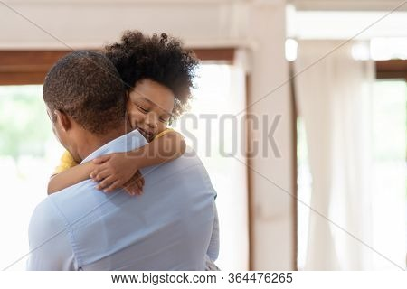 Happy African American Man Hugging With Little Kid Boy With Eyes Closed When He Arriving At Home. Bl
