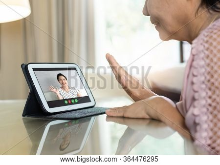 Asian Senior Woman Waving Hand And Talking To Her Relatives And Family Via Internet And Wireless Tec