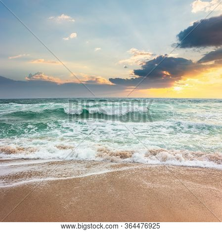 Storm On The Sandy Beach At Sunset. Dramatic Ocean Scenery With Cloudy Sky. Rough Water And Crashing