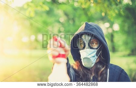 Woman wearing old hazmat style gas mask and medical mask, outside in bright summer environment, cleaning with spray bottle.