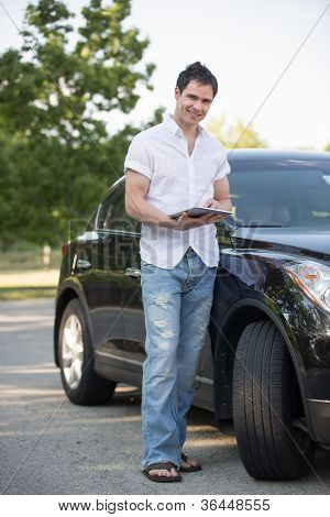 Male Driver Holding a Touch Pad Tablet PC by Car at Road Side