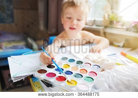 Small Child Sit At Kids Desk And Draw With Watercolors And Paint Brush, Homeschooling In Quarantine