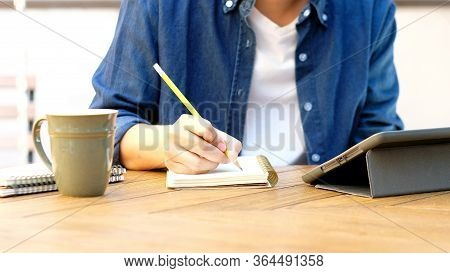 Online Studying Class, Student Man Hand Writing On Notebook While Using Digital Tablet For E Learnin
