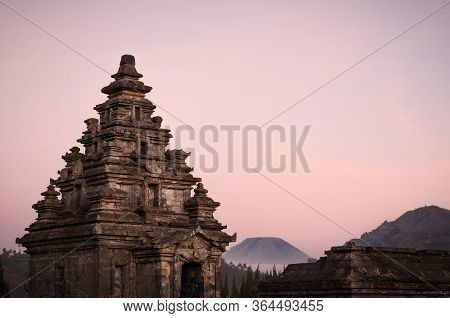 Roof Spires And Stone Carvings Of The Main Stupa In Candi Arjuna Temple Complex, With Volcano Crater