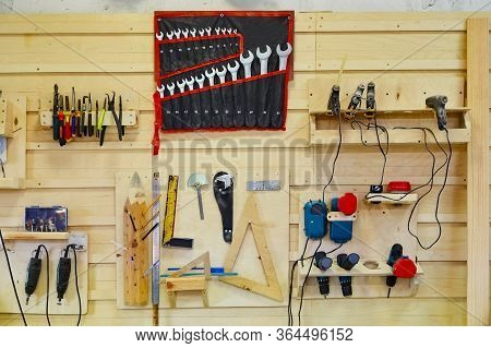 Tools Hanging On The Wall In A Carpentry Workshop. Wrenches, Screwdrivers, Pliers, Coals, Etc. Works