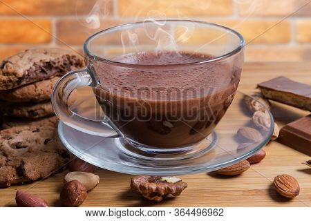 Foamed Hot Chocolate In Glass Cup On Saucer Among The Confections And Various Nuts Illuminated On Th