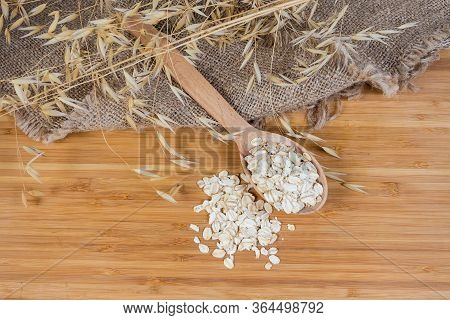 Uncooked Rolled Oats In The Wooden Spoon On The Bamboo Wooden Cutting Board Among The Oat Ears, Top