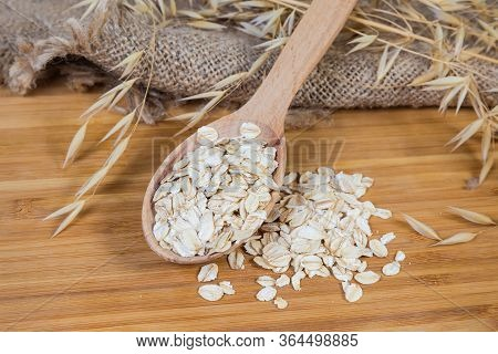 Uncooked Rolled Oats In The Wooden Spoon And Scattered Beside On The Bamboo Wooden Cutting Board Amo