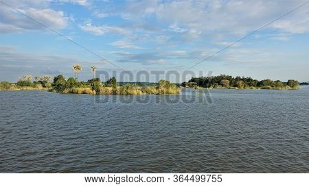 The Zambezi River Flows Calmly. On It Are Small Islands Covered With Grass, Bushes, Silhouettes Of P