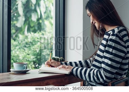 Asian Woman Write Plan To Do List On Notebook White Listening Music At Home In Quarantine Time