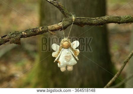 Figurine Of A Funny Little Angel Hanging On A Tree In The Forest