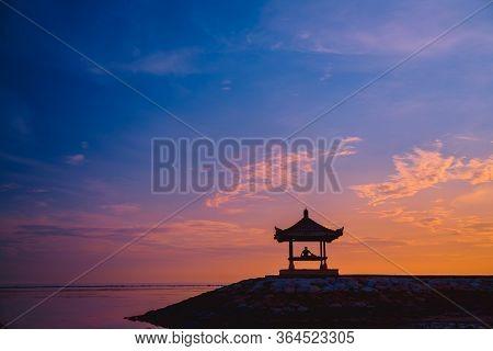 Silhouette Of A Man Sitting In A Gazebo On The Beach At Dawn On Sanur Beach, Bali, Indonesia. A Man