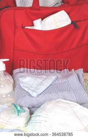 Big Red Diaper Bag With Newborn Accessories To Maternity Hospital. Diapers, Grey Plaid, Bottle And O