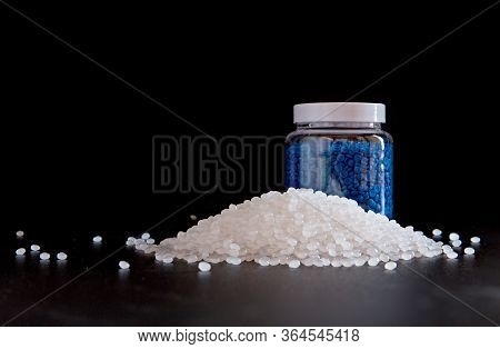 White Plastic And Blue Plastic Beads In Plastic Bottles On Black Background, Polymers Bead Or Polyme