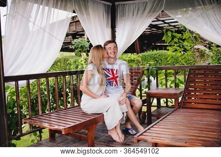Happy Young Kissing Couple In Gazebo In Nature. Sits On Bed In Wooden Installations For Recreation.