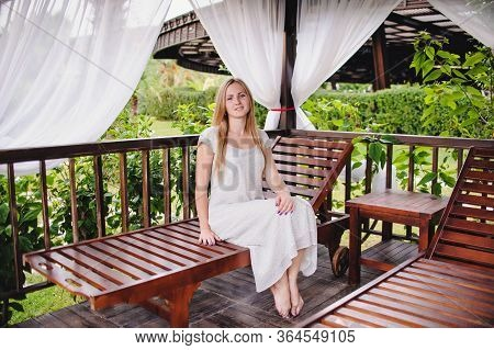 Beautiful Happy Young Slender Long-haired Blonde Girl In Gazebo. Woman Sits On Bed. Nature. Wooden I