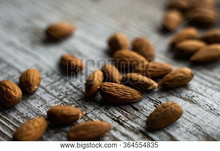 Almonds Scattered On The Wooden Vintage Table. Almond Is A Healthy Vegetarian Protein Nutritious Foo
