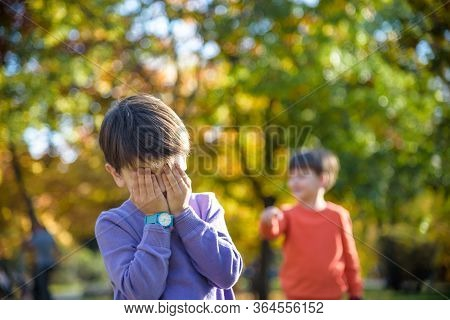 Pupil Bullying Another In The Yard At The Elementary School. Older Boy Offends Younger Kid. Laughing
