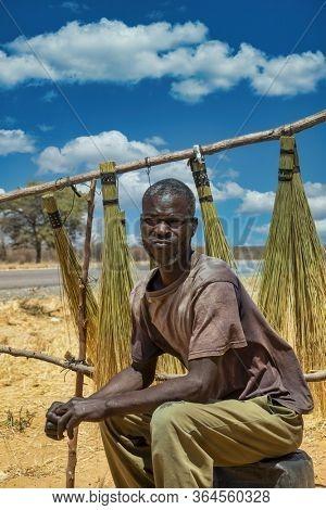 Motswana, African man trading hand made brooms, Kalahari in Botswana