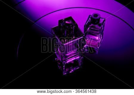 High Angle View Of Purple Perfume Bottles On Round Violet Mirror Surface