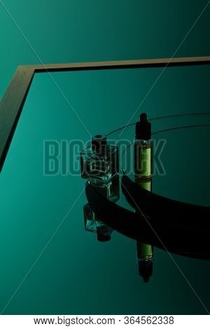 High Angle View Of Perfume Bottle And Serum Bottle On Dark Green Mirror Surface