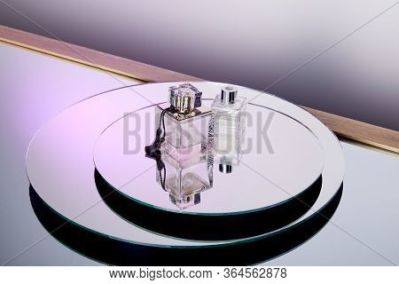 High Angle View Of Luxury Purple Perfume Bottles On Round Mirror Surface
