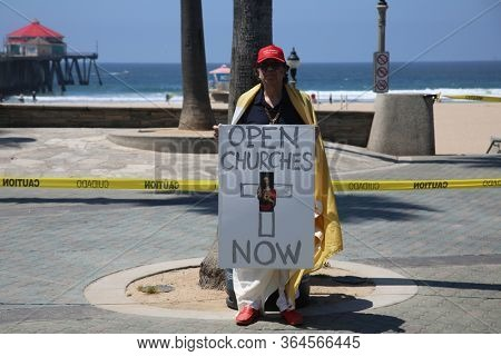 Huntington Beach, California / USA - May 1, 2020: People Protest Gov. Gavin Newsom's stay-at-home orders and beach closure. People Wave Flags, Hold Signs, Cheer and Police keep everyone safe.