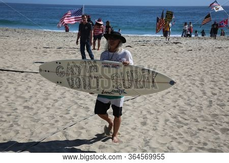 Laguna Beach, California / USA - May 2, 2020. #OpenUpCa. Various people smile, hold signs, flags, wave and cheer as they protest the Coronavirus Lock Down in Laguna Beach, California.
