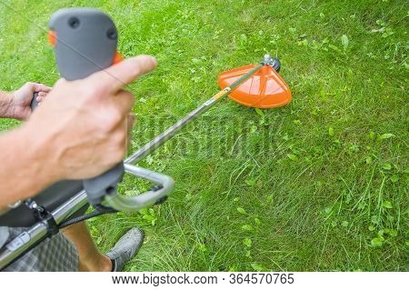 Guy With Lawn Mower In Front Of Back Yard.close Up Of Young Worker With A String Lawn Trimmer Mower