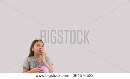 Young Sad Girl Play With Protective Medical Glove. Teenager With Glove Inflated Like Balloon. Quaran