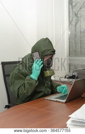 Man In A Biohazard Protective Suit Is Working On Computer And Talking On The Phone. Testing For Sars
