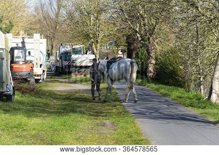 Sint Gillis Waas, Belgium, April 4, 2020, Man With Horse On Hand Must Pass Through Obstacle Of Vehic