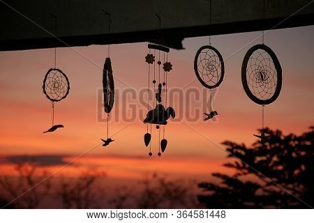 Handmnade decoration hanging on a balcony, dramatic red glowing twilight, sky
