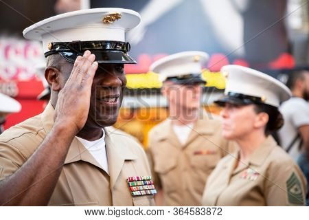 MAY 22 2019-NEW YORK: USMC officer salutes after a commemorative group photo on the red steps in Father Duffy Square during Fleet Week in Manhattan on May 22, 2019.