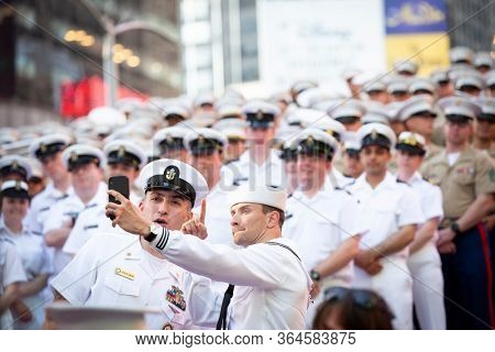 MAY 22 2019-NEW YORK: Sailors take a cellphone selfie with Sailors and Marines on the iconic red steps in Father Duffy Square for Fleet Week in Manhattan on May 22, 2019.