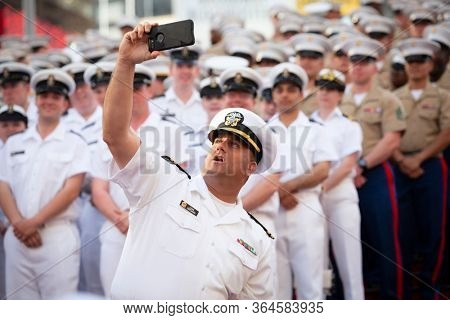 MAY 22 2019-NEW YORK: A U.S. Navy officer takes a cellphone selfie with Sailors and Marines on the red steps in Father Duffy Square for Fleet Week in Manhattan on May 22, 2019.