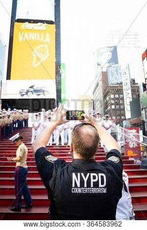 MAY 22 2019-NEW YORK: NYPD Counter Terrorism officer takes a cellphone picture of Sailors, Marines, and Coast Guardsmen on the iconic red steps in Father Duffy Square at Fleet Week, May 22, 2019.