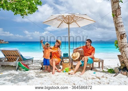 Family on beautiful Petite Anse beach, young couple with three year old toddler boy sitting on sun bed. Summer vacation at Seychelles, Mahe.