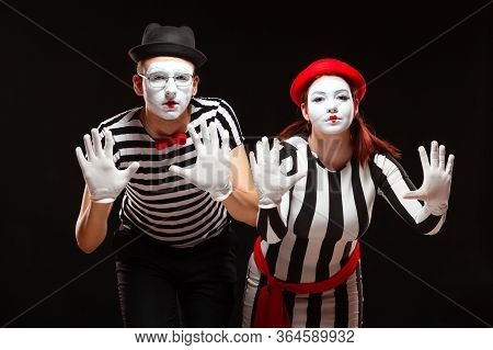 Portrait Of Man And Woman Mime Artists Performing, Isolated On Black Background. Mimes In Striped Cl